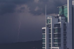 Photo of a building with an evening thunderstorm sky and a thin bolt of lightning in the background