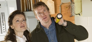 Photo of a woman and a home inspector in a basement
