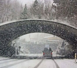 Car Driving Under Bridge in snow storm shows impact of climate adaptation