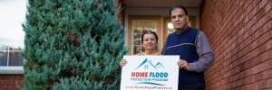 Home owners holding the Home Flood Protection Program sign outside of brick home