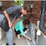 Flood Risk Assessor Larry Freiburger invites homeowner Lindsay Bunce to use the audible moisture meter.